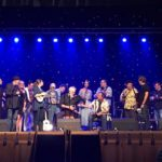 Photo of 14 performers on a stage. Some holding ukes.